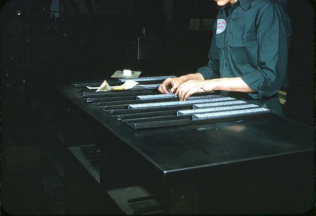 Homme en train de ranger les lettres qui servent à l'impression typographique.